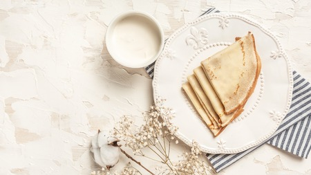 Crepes, thin pancakes with honey on a white plate. Top view. Flat lay. space for text. 免版税图像