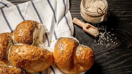 Homemade challah bread with sesame seeds on wooden background. Traditional jewish bread. Rustic concept. Stock Photo