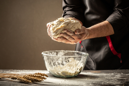 An experienced chef in a professional kitchen prepares the dough with flour to make the bio Italian pasta. the concept of nature, Italy, food, diet and bio. Food concept.