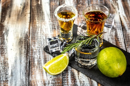 Set of strong alcoholic drinks in shot glass on rustic wood background. space for text. concept luxury drink.