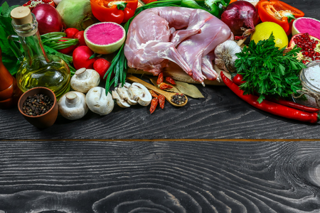 raw rabbit on a wooden Board with ingredients on a wooden background - top view. Concept of Dietary Nutrition.
