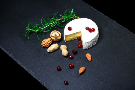 Brie type of cheese. Camembert cheese. Fresh Brie cheese and a slice on a shale board with nuts, berries and leaves. Italian, French cheese. 写真素材