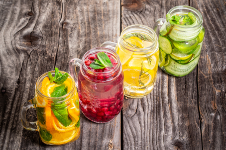 Fresh lemonade with mix of fruits in sunny day on a wooden background. Health care, fitness, healthy nutrition diet concept.