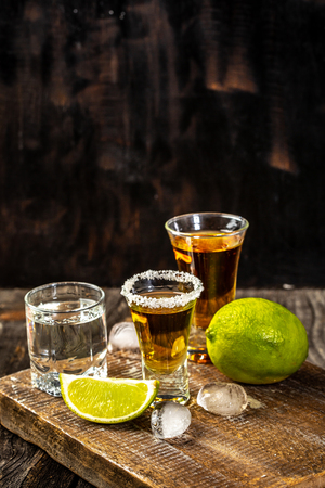 Alcoholic drink concept. Mexican tequila with lime and salt on rustic wood background. space for text. concept luxury drink. Zdjęcie Seryjne