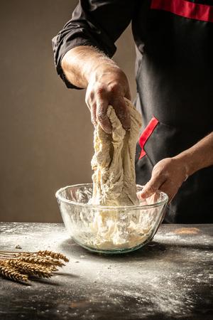 Les mains des hommes saupoudrent une pâte de farine de près. Homme préparant la pâte à pain. image verticale. espace pour le texte.