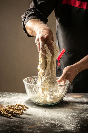 Men hands sprinkle a dough with flour close up. Man preparing bread dough. vertical image. space for text.
