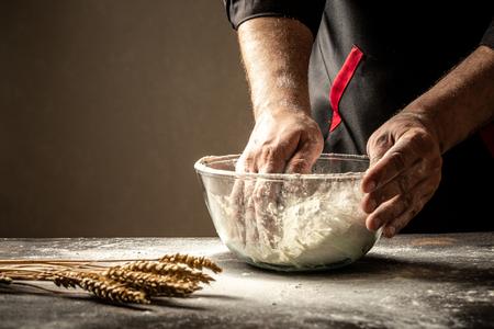 Préparation de la pâte. Préparation de la pâte les mains des hommes. Sur une table en bois. Notion de nourriture.