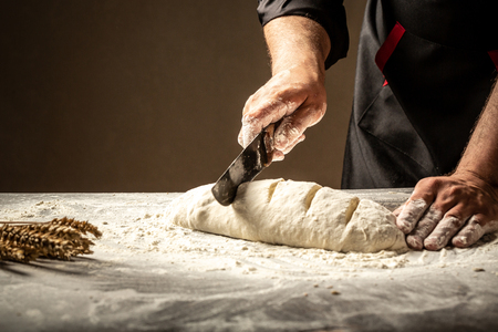 Baker making patterns on raw bread using a knife to shape the dough prior to baking. Manufacturing process of spanish bread. Food concept. Stockfoto