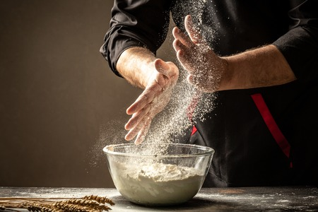 Powdery flour flying into air as man in black chef outfit wipes off his hands over table covered in flour. White flour flying into air. Food concept. Reklamní fotografie