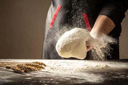 man clapping and sprinkling flour over dough on table. White flour flying into air. space for text. Stockfoto