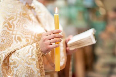 Während der Taufe brennt eine hohe Kerze hinter einem schönen Kind. Das Sakrament der Taufe. Attribute eines orthodoxen Priesters für die Taufe.