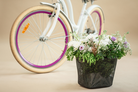 pink vintage bicycle with flower basket isolated on white background.