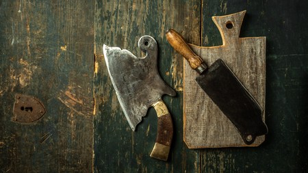 Rustic table with vintage meat cleaver on wooden background with copy space. Food concept.