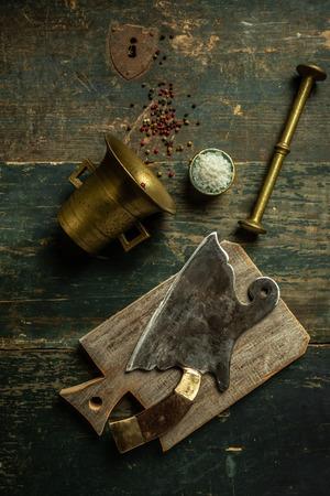 Vintage meat knife hatchet on vintage chopping board and black stone table background. Butcher utensils. Food concept recipe menu.