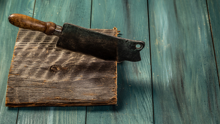 Butcher. Vintage meat knife on dark wooden background with copy space. Food concept recipe menu.