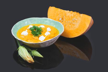 Homemade pumpkin puree in a bowl. Pumpkin soup and organic pumpkins, top view, copy space. Seasonal autumn food - Spicy pumpkin soup with croutons and pumpkin seeds.