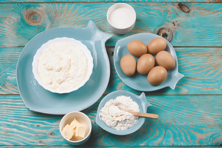 Ingredients and cooking tools for biscuit. Flour, sugar, butter, eggs. blue food background. Food concept. Top view Copyspace for text.