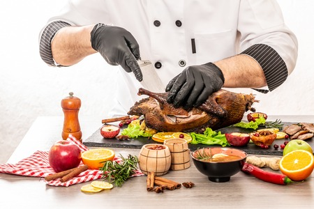 Roast Christmas duck with thyme and apples on rustic wooden table. Thanksgiving or Christmas Dinner. The chef is cutting the duck.