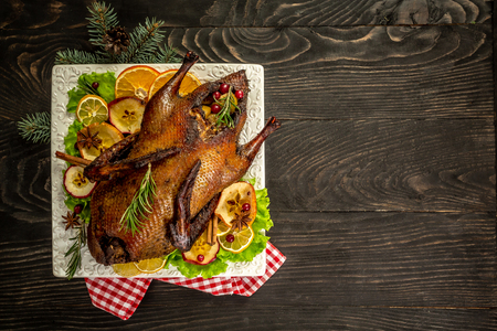 Roast Christmas duck with thyme and apples on rustic wooden table. Thanksgiving or Christmas Dinner. top view. place for text.