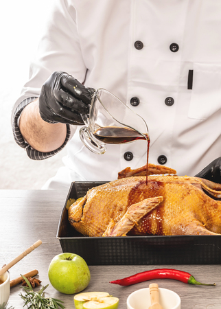 Chef serving baked duck with oranges and apples. delicious and healthy food in the home kitchen for christmas.
