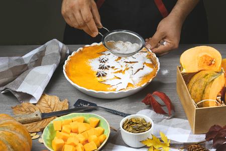 Pumpkin pie, tart made for Thanksgiving day. Fresh round bright orange homemade pumpkin pie in baking dish.