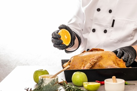 chef cooking a festive duck for the Christmas, New Years Eve dinner. Preparing fresh duck stuffed with apples. place for text.