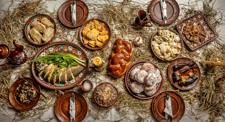 Flat lay of Delicious Christmas themed dinner table. twelve meatless dishes in Ukraine, Belarus and Poland, on wooden table.