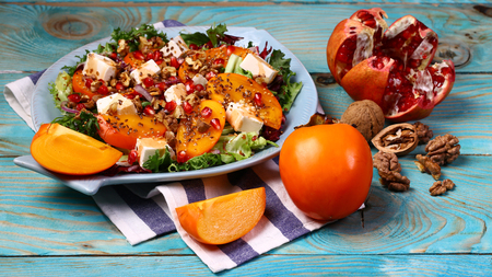Salad with persimmon, arugula, pomegranate seeds, nuts, dried cranberry, blue background. Flat lay copy space