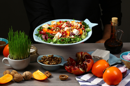 Chef hands cooking Fresh salad with fruits and greens. Salad with persimmon, arugula, pomegranate seeds, nuts. Reklamní fotografie
