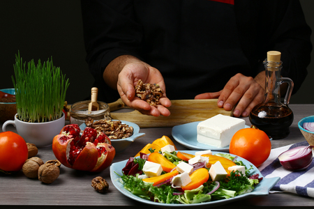 Chef hands cooking Tasty Persimmon and pea shoot salad with walnuts, pomegranate and pumpkin seed.