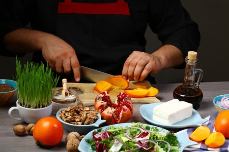 Chef hands cooking Autumn salad with persimmon, pomegranate, blue cheese and walnuts . Reklamní fotografie