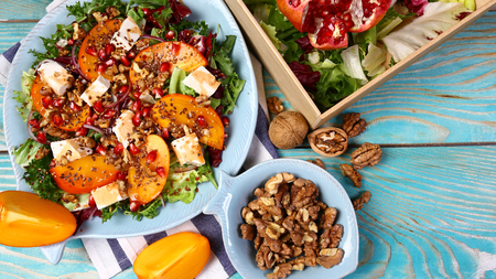 Fresh autumn salad with persimmon, arugula, cheese and pomegranate seeds. Space for copy