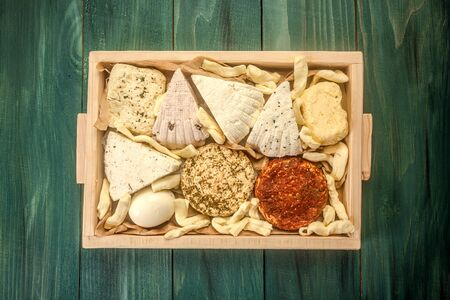Various dairy products. Assorted cheeses in a wooden box. top view.