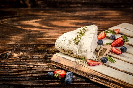 soft cheeses with fragrant herbs. Adyghe cheese with fresh berries, on rustic background. space for text.