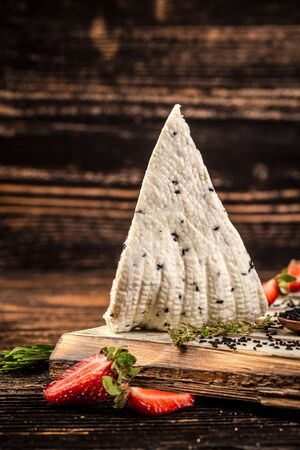 Adyghe cheese with black cumin. cream, cottage cheese on rustic background. space for text.