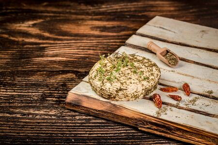 Soft goat cheese with herbs on the old blue wooden table. Rustic Style Goat Cheese. space for text.
