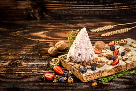 soft cheese with walnut. Adyghe cheese with fresh berries, on rustic background. space for text. 写真素材