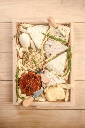 Various dairy products. Assorted cheeses in a wooden box. Circassian curd cheese. top view.