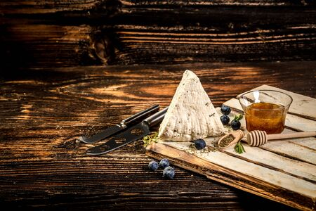Soft Adyghe cheese with fresh berries, honey on rustic background. space for text. 写真素材
