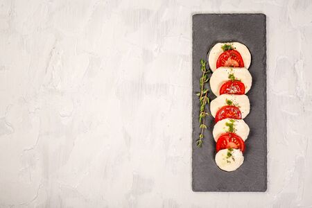 Mozzarella cheese, basil and tomato cherry on slate stone board, copy space. Ingredients for Caprese salad on cutting board. Top view. Free space for your text 写真素材