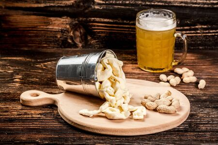 Glass of beer and cheese on brown vintage background. snack for beer. pace for text