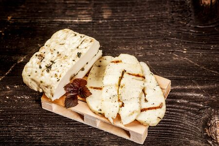 Halumi cheese on a wooden background. Preparation of cheese Halumi. Cheese Halumi with mint