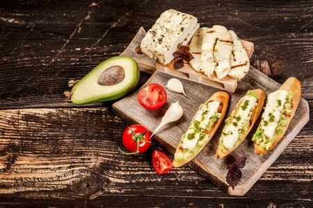 bruschetta with grilled cheese halumi, avocado and cherry on a wooden background. Preparation of cheese Halumi. Cheese Halumi with mint.