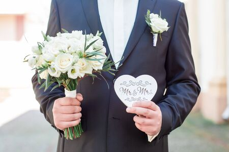 Groom holding wedding rings, the groom in a grey suit, groom holding wedding rings, wedding ring in groom hand. 写真素材