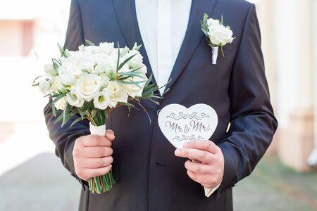 Novio con anillos de boda, el novio con un traje gris, novio con anillos de boda, anillo de bodas en la mano del novio. Foto de archivo