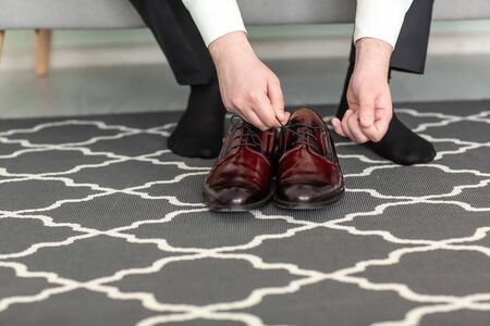 An elegant man puts on black, leather, formal shoes. Tying shoes. The morning of the groom.