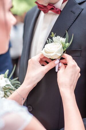 The bride's hand puts on a boutonniere flower on the groom's jacket. Bride puts a buttonhole on a grooms suit. close-up. Reklamní fotografie - 125525618