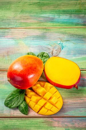 Mango tropical fruit on a dark wooden background. Flat lay. place for text. Food concept. vertical image.
