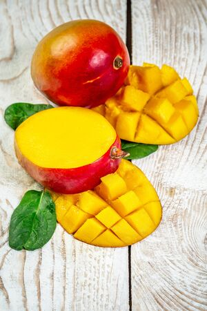 Famous Alphonso mango slices over wood background, vertical image. Top view.