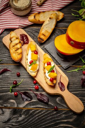 Cooking Bruschettas with cheese, Alphonso mango. Bruschetta with mango and cheese. Homemade. Healthy vegetarian nutritionon a wooden background, Top view. 写真素材